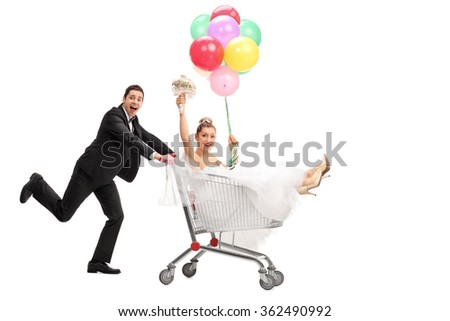 Full length portrait of a groom pushing the bride in a shopping cart isolated on white background - stock photo