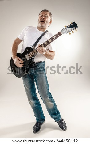 Full length portrait of a guitar player exciting music on gray background - stock photo
