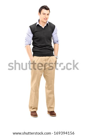 Full length portrait of a guy standing with hands in his pockets looking at camera, isolated on a white background