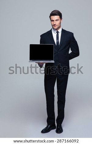 Full length portrait of a handsome businessman showing blank laptop screen over gray background and looking at camera - stock photo