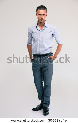Full length portrait of a handsome businessman standing on gray background and looking at camera - stock photo