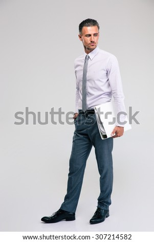 Full length portrait of a handsome businessman standing with folder isolated on a white background - stock photo