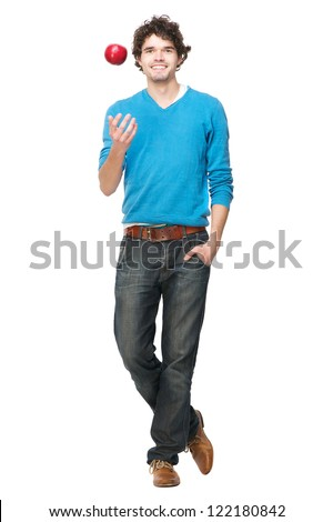 Full length portrait of a handsome casual young man throwing an apple up. Isolated on white background - stock photo
