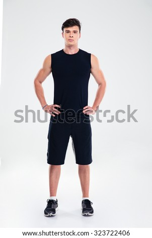 Full length portrait of a handsome man in sports wear standing isolated on a white background and looking at camera - stock photo