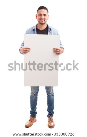 Full length portrait of a handsome young Hispanic man holding a white sign and smiling - stock photo