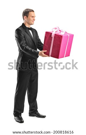Full length portrait of a handsome young man holding a big present isolated on white background - stock photo