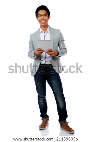 Full length portrait of a happy asian man holding tablet computer over white background - stock photo