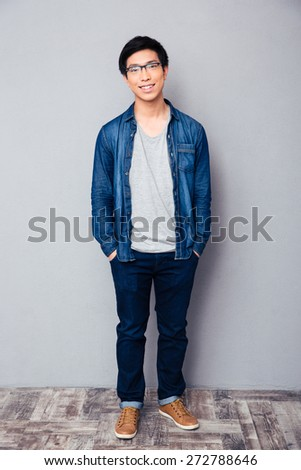 Full length portrait of a happy asian man standing with hands in pockets  - stock photo