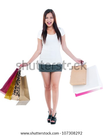 Full length portrait of a happy Asian woman carrying shopping bags over white background.