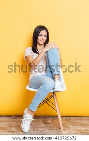 Full length portrait of a happy attractive woman sitting on the chair over yellow background - stock photo