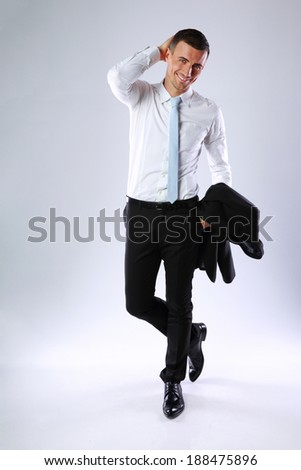Full length portrait of a happy business man holding jacket on gray background - stock photo
