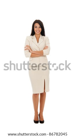 Full length portrait of a happy business woman standing with folded hands in modern suit isolated over white background - stock photo