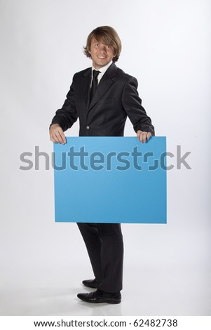Full length portrait of a happy businessman holding a blue blank banner with room for text. Studio shot. See more in my portfolio