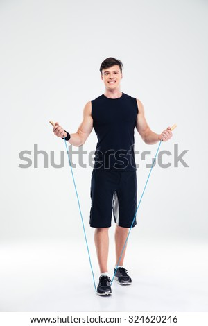 Full length portrait of a happy fitness man workout with jumping rope isolated on a white background - stock photo