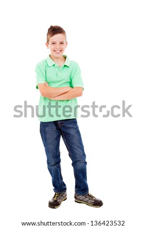 Full length portrait of a happy little boy standing with folded arms over white background - stock photo
