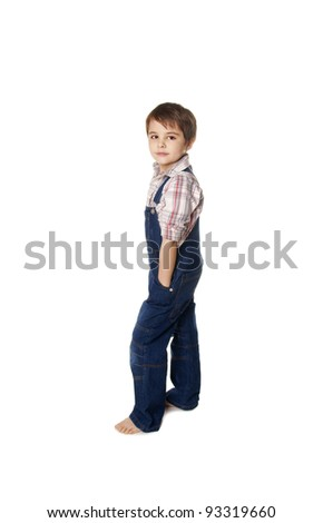 Full length portrait of a happy little boy standing with hands in pockets on white background