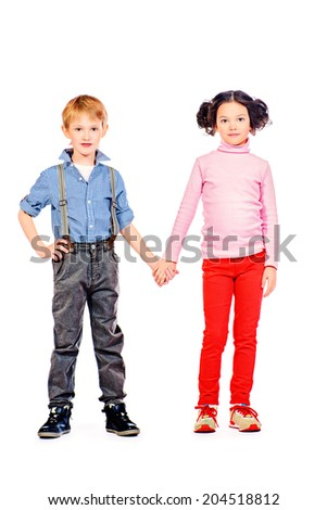 Full length portrait of a happy little girl and boy standing together. Children. Isolated over white. - stock photo