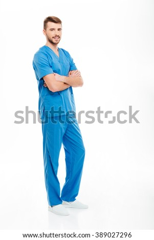 Full length portrait of a happy male doctor standing with arms folded isolated on a white background - stock photo