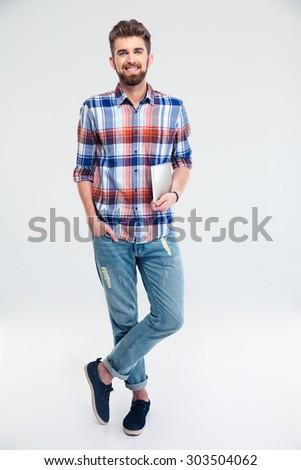 Full length portrait of a happy man standing with tablet computer isolated on a white background. Looking at camera - stock photo