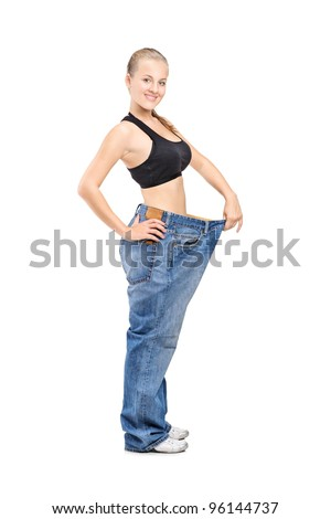 Full length portrait of a happy weight loss female holding her old jeans isolated on white background - stock photo