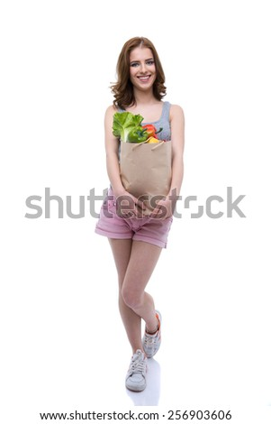 Full length portrait of a happy woman holding a shopping bag full of groceries - stock photo