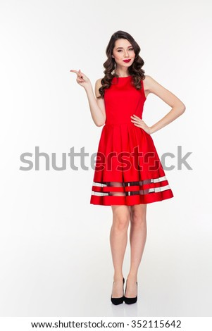 Full length portrait of a happy woman in red dress pointing finger away isolated on a white background - stock photo