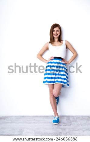 Full length portrait of a happy woman leaning at the white wall - stock photo