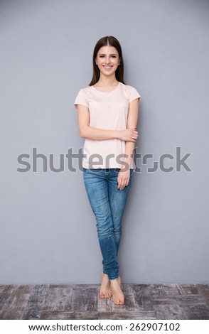 Full length portrait of a happy woman leaning on the wall - stock photo