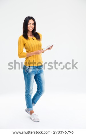 Full length portrait of a happy woman standing and holding tablet computer isolated on a white background. Looking at camera  - stock photo