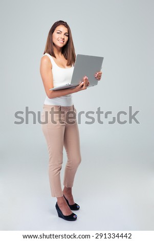 Full length portrait of a happy woman standing with laptop over gray background - stock photo