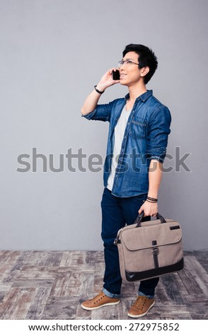Full length portrait of a happy young asian man talking on the phone  - stock photo