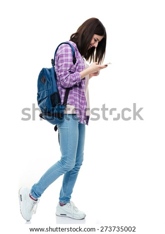 Full length portrait of a happy young female student using smartphone over white background - stock photo