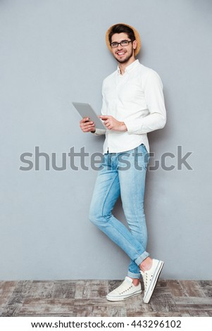 Full length portrait of a happy young man using tablet computer isolated on a gray background - stock photo