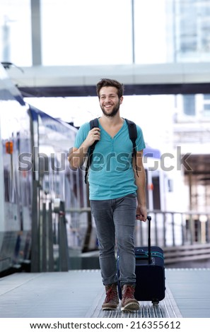Full length portrait of a happy young man walking with suitcase at train station - stock photo