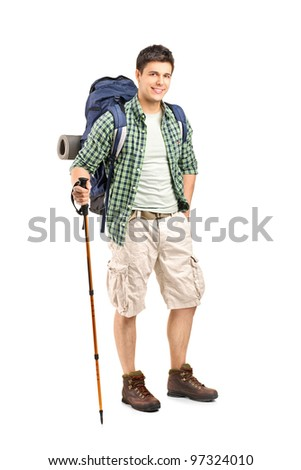 Full length portrait of a hiker with backpack and hiking poles posing isolated on white background