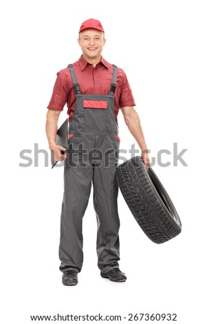 Full length portrait of a joyful mechanic in a gray jumpsuit, holding a tire in one hand and a clipboard in the other isolated on white background - stock photo