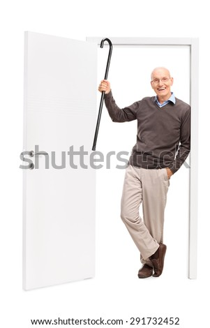 Full length portrait of a joyful senior showing his cane and leaning on the frame of an open door isolated on white background - stock photo