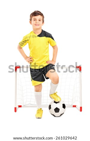 Full length portrait of a junior soccer player standing in front of a small goal isolated on white background - stock photo