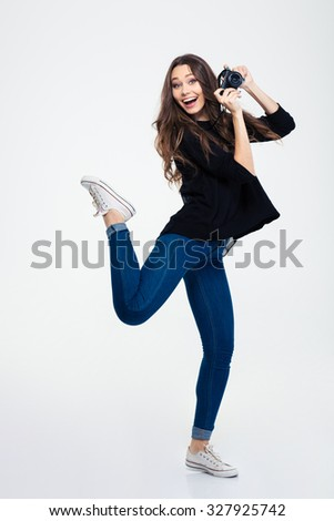 Full length portrait of a laughing casual woman posing with photo camera isolated on a white background - stock photo