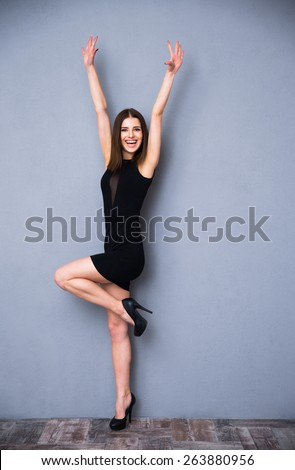 Full length portrait of a laughing cute woman in fashion black dress. Posing over gray background. With raised hands up. Looking at camera. - stock photo