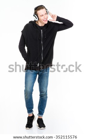 Full length portrait of a laughing man with headphones standing isolated on a white background and looking away - stock photo