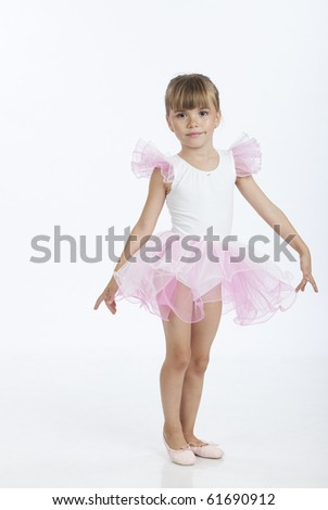 Full length portrait of a little ballerina learning a new ballet position, studio image
