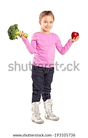 Full length portrait of a little girl holding a broccoli and an apple isolated on white background