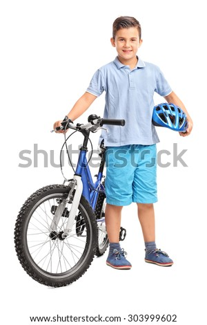 Full length portrait of a little kid posing with his bicycle and holding a blue helmet in his hand isolated on white background - stock photo
