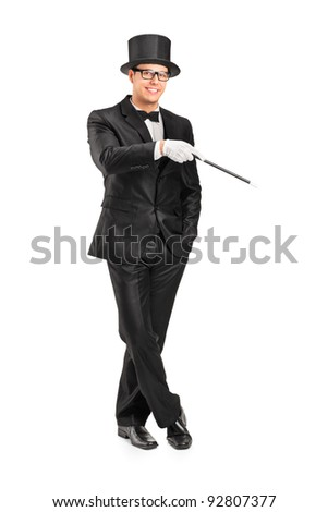 Full length portrait of a magician holding a magic wand posing isolated on white background - stock photo