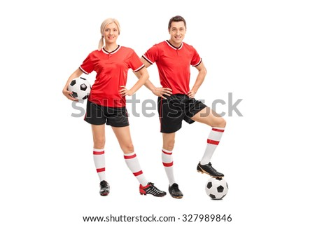 Full length portrait of a male and female football players in red jerseys looking at the camera isolated on white background - stock photo