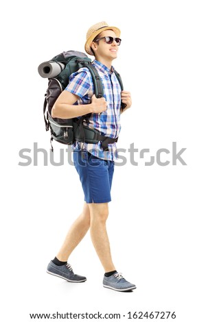 Full length portrait of a male hiker with backpack walking isolated on white background - stock photo