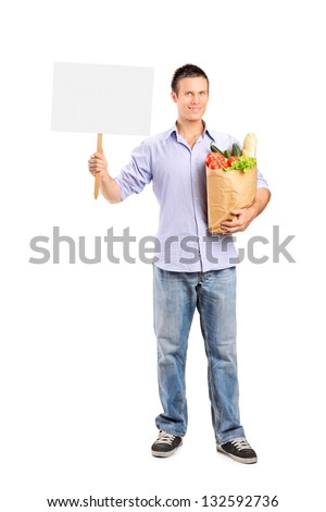 Full length portrait of a male holding a paper bag and blank panel isolated on white background - stock photo