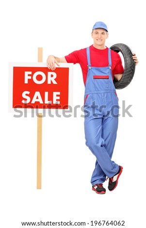 Full length portrait of a male mechanic standing by a for sale sign isolated on white background