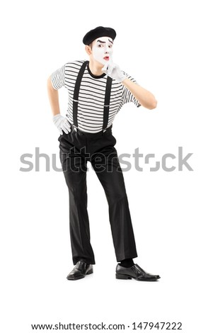 Full length portrait of a male mime artist gesturing silence with a finger on his mouth, isolated on white background - stock photo